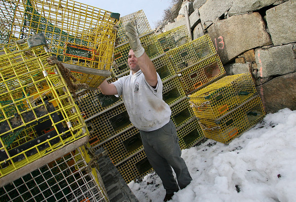 Rockport: Ryan Drohan stacks his lobster traps at Granite Pier after taking them out of the water for the remainder of the winter season. Drohan says he usually keeps the traps out all winter, but the economy and low price for lobster this year changed that. Photo by Kate Glass/Gloucester Daily Times Thursday, February  12, 2009