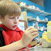 Gloucester: Jake Reardon, 8, of Gloucester paints a school bus cookie jar at Glazed Ceramics Studio Friday afternoon. Reardon got some help from his mom painting the bus yellow since he had a lot of detail work to do. Mary Muckenhoupt/Gloucester Daily Times