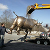 Essex: A backhoe lifts a broze rhino made by Chris Williams, left, and Phil Palminteri, right, in front of the Essex Elementary School Friday afternoon. The 1,800 lb. rhine was lifted onto four dollies and pushed into the school cafeteria for Messy Art Night. Mary Muckenhoupt/Gloucester Daily Times