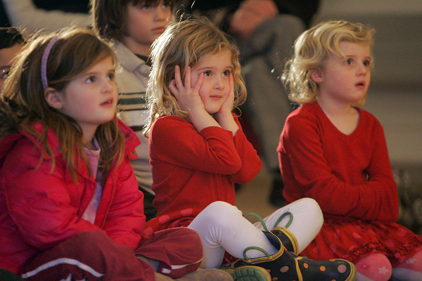 Manchester: From left Isabel Smail, 6 and her sisters Allie and Ashley, both age 4, watch the Woodland Cinderella Puppet Show put on by Deborah Costine at the First Parish Chapel Saturday afternoon. Allie, center, was nervous when the wicked step-mother would yell at Cinderella. The program was put on by the Manchester Public Library. Mary Muckenhoupt/Gloucester Daily Times