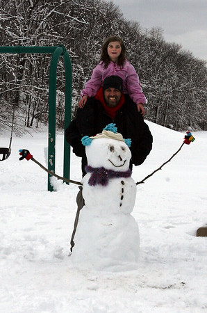 Gloucester: Maya Churchill and her Uncle Brian stand behind a snowman they made at the Green Street Playground on Wednesday. Photo by Kate Glass/Gloucester Daily Times