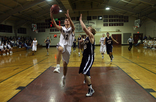 Rockport: Rockport's Tom Burnham leaps above Lynnfield's Freddie Shove at Rockport High School last night. Photo by Kate Glass/Gloucester Daily Times