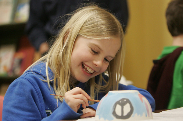 Gloucester: Jenna Lake, 9, of Gloucester works on painting her bowl while laughing with friends at The Open Door Food Pantry Thursday night.  The Open Door Food Pantry along with North Shore 104.9 helds it's first bowl decorating event for the annual Empty Bowl Dinner. Mary Muckenhoupt/Gloucester Daily Times