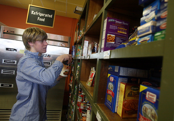 Gloucester: Ryan Bakerdunn, a volunteer from St. Johns Prep, stocks shelves at the Cape Ann Open Door Food Pantry yesterday afternoon. The non-profit purchased the Emerson Ave. building it has been renting from Wellspring, Inc. Photo by Kate Glass/Gloucester Daily Times