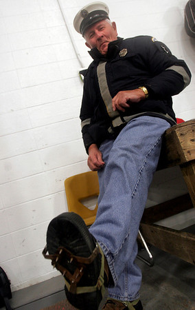 Gloucester: Frank La France, who has been the EMT for all Gloucester football and hockey home games for 37 years, shows the crampons he uses to reach players out on the ice. Photo by Kate Glass/Gloucester Daily Times