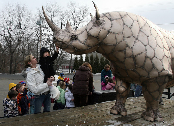 Essex: Jennifer Gaskell picks up Hannah Shields of Essex so she can touch a large bronze rhinocerus made by Essex sculptor Chris Williams. Williams brought the statue to Little Sprouts yesterday morning and will bring it to Essex Elementary School for their Messy Art Night on Friday. More than fifteen artists from around Cape Ann will be participating in the event, which runs from 5:30-7:30. Photo by Kate Glass/Gloucester Daily Times