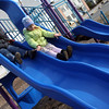 Gloucester: John Recroft and his neighbor, Lucy Shea, race down the slides at Rebecca's Playground in Lanesville on Monday afternoon. Photo by Kate Glass/Gloucester Daily Times