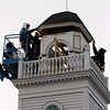 Manchester: Richard Levesque, left, of American Steeple & Tower Company, and Bill Bazel and Sam Scola, who work with restorationist Stan Magnuson, guide the roof of Seaside No. 1's hose tower as it is hoisted off by a crane yesterday afternoon. The tower is being removed for restoration and will hopefully be back in the spring. Photo by Kate Glass/Gloucester Daily Times