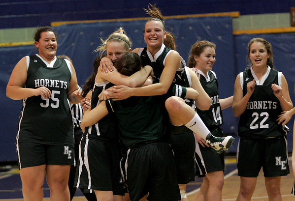 Everett: Manchester Essex's Lizzy Ball leaps on her teammates as the Hornets celebrate their win over Pope John in the first round of the MIAA North Division IV Tournament at Pope John last night. The Hornets will play Minuteman on Saturday at 7. Photo by Kate Glass/Gloucester Daily Times