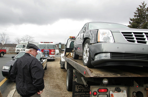 Gloucester:  Joe McCarthy looks at the cadillac his wife was driving as it gets lifted on a tow truck at Grant Circle Wednesday afternoon. A tractor-trailer ran the car off the road but there were no injuries. Mary Muckenhoupt/Gloucester Daily Times