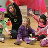 Manchester: Amelia Costa, 3, center, holds hands with Bella Wright, 4, as Tamara Hey of Leeney and Tamara sings with a group of children which also included Maeve Pleuler, 8, left, and Ani Stephan, 3, during the ice-cream social for Haiti hosted by Captain Dusty's Ice Cream at the Manchester Community House Saturday. Mary Muckenhoupt/Gloucester Daily Times