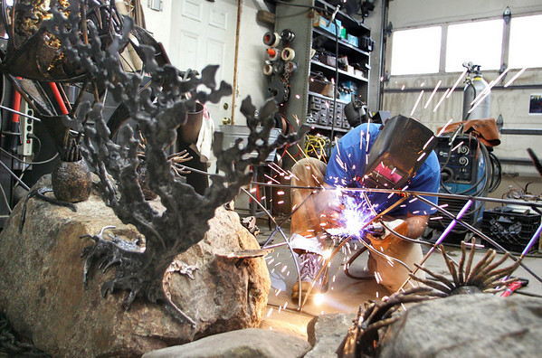 Essex: Phil Palminteri works on an ocean themed sculpture created by Chris Williams that will be hung at Logan Airport in the next few weeks. Palminteri and Williams have been working on the sculpture in William's garage in Essex.  Mary Muckenhoupt/Gloucester Daily Times
