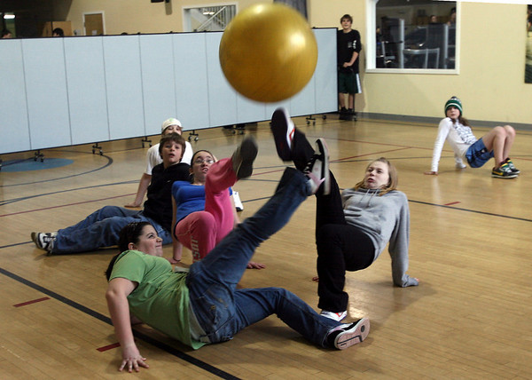 Manchester: Kate Parisi, Nicole Williamson, and Hannah LeClerc, all 7th grade students at the O'Maley Middle School, all reach for the ball as they play soccer doing the crab walk during the enrichment program at the Manchester Athletic Club on Wednesday. The students learned about nutrition and physical fitness during the program. Photo by Kate Glass/Gloucester Daily Times