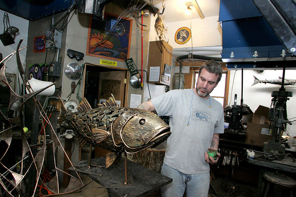 Essex: Chris Williams stands with the only part of the sculpture that will be hung on the wall at Logan Airport in his Essex garage Wednesday. The rest of the metal, glass and rock art work will go on the floor. Mary Muckenhoupt/Gloucester Daily Times