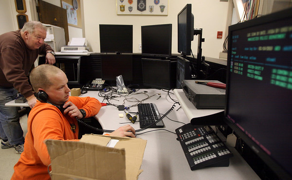 Manchester: Manchester Police Detective Rick Newton installs radio equipment in their new dispatch desk at the Police Station as retired Sgt. David Metrano looks on. Photo by Kate Glass/Gloucester Daily Times
