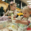 Essex: Alexis Garfield, 2, and her sister Christina Lynn, 4, play in some colored foam, or shaving cream, during Messy Art Night at the Essex Elementary School Friday night.  About 20 local artists came to provide hands-on demonstrations for kids for anythign from woodworking to pottery. Mary Muckenhoupt/Gloucester Daily Times