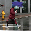 Gloucester: Patricia Foster's umbrella get's blown inside out as she crosses Pleasant Street Thursday afternoon. Rain and snow showeres are expected to continue today, tomorrow and Sunday with sunshine returning the beginning of next week. Mary Muckenhoupt/Gloucester Daily Times