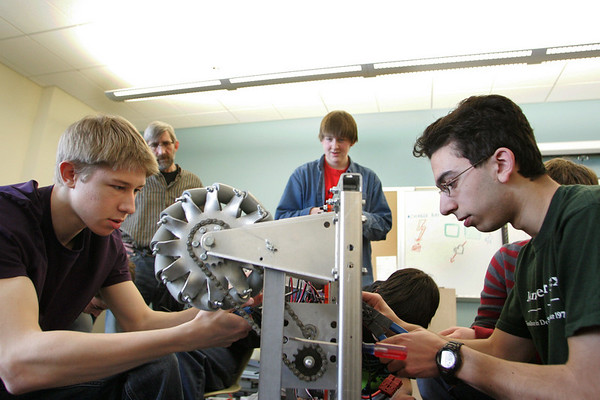 Manchester: Students from the robotics team, including senior Greg Neff, left, and sophomore Peter Goulakos, right, work on the robot they have built that has the abilty to kick a soccer ball at Manchester Essex Regional High School. The students are getting ready for a competition in March at the Agganis Arena at Boston University. Mary Muckenhoupt/Gloucester Daily Times