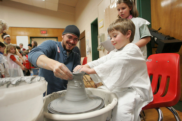 Essex: Sam Roberts, 4, throws clay for the first time with the help of Phil Scheer from Art Haven in Gloucester during Messy Art Night at Essex Elementary School Friday night. Mary Muckenhoupt/Gloucester Daily Times
