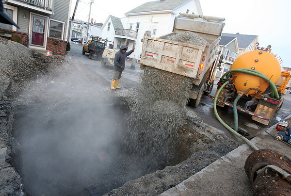 Gloucester: A crew from the Gloucester DPW fills in the hole after repairing a water main leak on Western Avenue yesterday. Traffic was detoured to the other side of the road while the work was completed. Photo by Kate Glass/Gloucester Daily Times