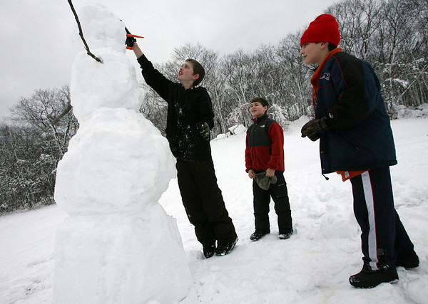 Gloucester: Alex La Belle puts the eyes on a six foot snowman that he and his friends, Devin Gadbois, center, and Joseph Billante, right, built at the Ganine Nancy Doucette Playground off Green Street. The three boys made a ramp to lift the large snowballs into place and used a step to put on the finishing touches. Photo by Kate Glass/Gloucester Daily Times