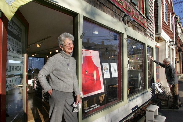 Rockport: Mary Ann Wenniger stands in the doorway of her gallery, Wenniger Gallery, that she has owned with her husband Mace, who is washing the front window, left. After being open for 39 years the Rockport gallery is closing on Tuesday after one last retrospective art show this weekend of promotional posters done by Davis Hruby of Gloucester. Mary Muckenhoupt/Gloucester Daily Times