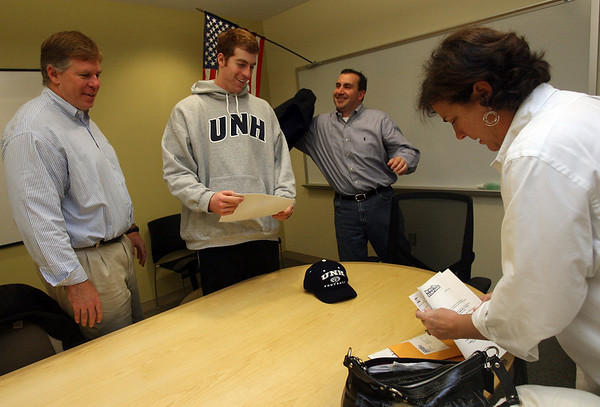 Manchester: Manchester Essex football captain Brian Ciccone smiles after signing his letter of intent to attend and play football at the University of New Hampshire during National Signing Day yesterday as his father, Tony Ciccone, coach Mike Athanas, and mom, Pam Ciccone look on. Photo by Kate Glass/Gloucester Daily Times