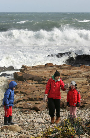 Gloucester: Sarka Jones shows her kids Philip, 7, and Christina 9, some lobster traps that washed ashore while checking out the waves on the back shore on Atlantic Road Friday afternoon. Mary Muckenhoupt/Gloucester Daily Times