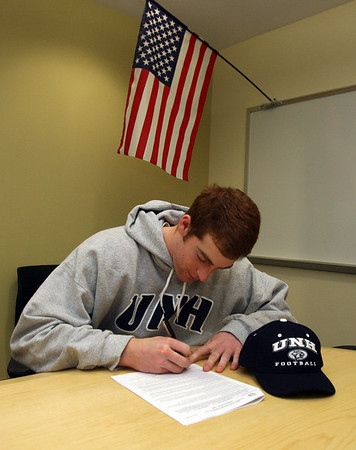 Manchester: Manchester Essex football captain Brian Ciccone signs his letter of intent to attend and play football at the University of New Hampshire during National Signing Day yesterday. Photo by Kate Glass/Gloucester Daily Times