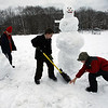 Gloucester: Joseph Billante, left, Alex La Belle, center, and Devin Gadbois, right, clear the snow away from their snowmen at the Ganine Nancy Doucette Playground on Green Street. The three were making a family, including one snowman that was over six feet tall. Photo by Kate Glass/Gloucester Daily Times