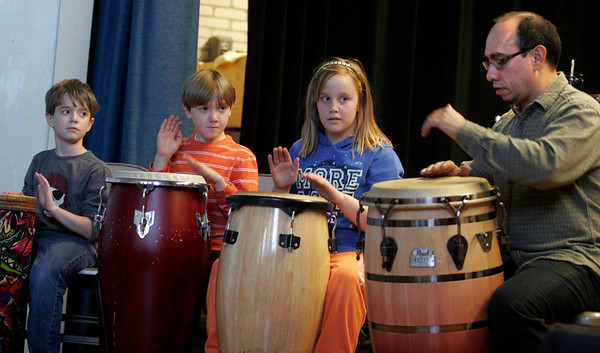 Gloucester: Brandon Smith, Miles Kressley and Ruby Melvin listen as Ernesto Diaz, a professor at Berklee, plays a beat for them to repeat at West Parish Elementary School yesterday. The program was sponsored by Rockport Music. Photo by Kate Glass/Gloucester Daily Times