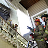 Gloucester: Captain Matteo Logrande and Doug McArthur, right, stand and assess the damage of a fire on 18 Conant Avenue Thursday morning. Mary Muckenhoupt/Gloucester Daily Times