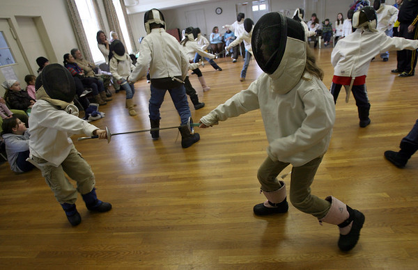 Manchester: Emerson Kahle, 6, and his sister, August Kahle, 8, learn how to fence during a program sponsored by the Manchester Public Library yesterday afternoon. Jack Mullarkey of 3MB Fencing discussed the different types of swords used in fencing and let the kids try out the gear. Photo by Kate Glass/Gloucester Daily Times