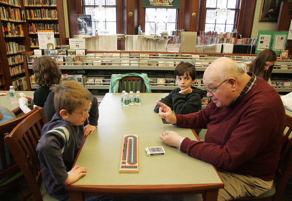 Manchester: Roger DiNapoli teaches William Pollock, 8, and William Russo, 8, left, how to play cribbage at the Manchester Public Library Thursday afternoon.  The Seniors and Students Cribbage Club is held on Thursday afternoons and registration is required. Mary Muckenhoupt/Gloucester Daily Times