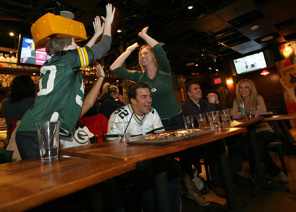 Gloucester: Colleen VonHaden high fives Gunnar VonHaden and Emily Vien as Mike Vien cheers after the Green Bay Packers score a touchdown during the Super Bowl last night. Colleen, who is originally from the Green Bay area, was watching the game at the Minglewood Tavern at Latitude 43. Photo by Kate Glass/Gloucester Daily Times
