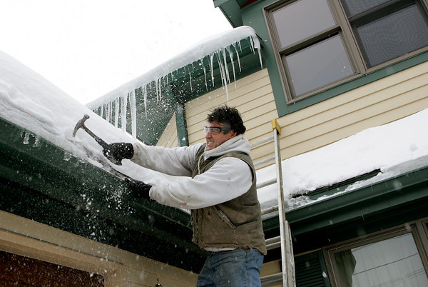 Gloucester: Desi Smith, photographer corespondent for the Gloucester Daily Times, chips away at the 6 inches of ice that has built up on his gutters Saturday afternoon.  Smith began tackling the job when water started to leak into his home.  Mary Muckenhoupt/Gloucester Daily Times