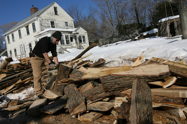 Essex: Pierre Erhard cuts wood for the steam furnace, which is used to make planks pliable for the schooner Ardelle. Photo by Kate Glass/Gloucester Daily Times