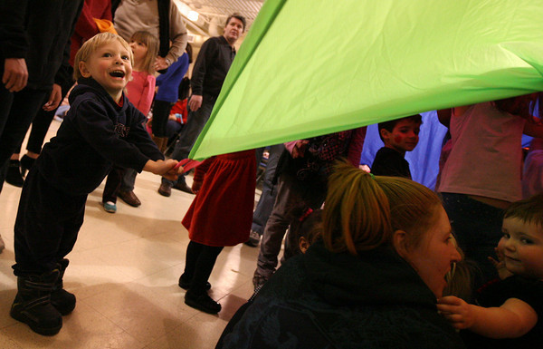 Gloucester: Jayden Chadwick, 2, smiles as he helps lift a parachute above other kids at Pathways for Children Thursday night during a free performance by Leeny & the Eeny Meenys. Photo by Kate Glass/Gloucester Daily Times