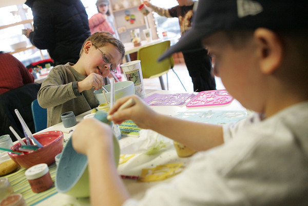 Gloucester: Matthew Angelino, 4, left, and his brother John, 7,  work on painting their bowls while enjoying a rainy afternoon at Glazed Friday. Mary Muckenhoupt/Gloucester Daily Times