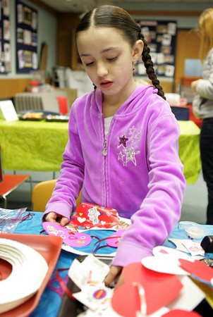 Gloucester: Ava Vitale, 6, works on making a Valentine's Day wreath with paper hearts and stickers during a Valentine's Craft hour at the Sawyer Free Library Saturday afternoon. Mary Muckenhoupt/Gloucester Daily Times