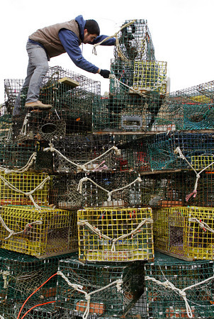 Gloucester: Yuichi Watanabe works on taking down the lobster trap tree on Main Street Saturday morning.  David Brooks, who was also working on taking the traps down said they would only be able to do so much since the bottom 2 layers were still covered in ice and snow. Mary Muckenhoupt/Gloucester Daily Times