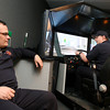 Gloucester: Gloucester Firefighter Domenic Gambale watches as Firefighter/Paramedic Nicholas Ouellette goes through a driving safety simulator program at Central Station yesterday. The simulator, which is provided by the Massachusetts Interlocal Insurance Association, is designed to reduce the risk of accidents and lower the town's insurance costs. Photo by Kate Glass/Gloucester Daily Times