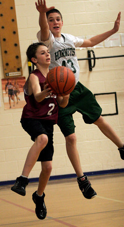 Essex: Rockport's Peter McManus dribbles around Manchester Essex's Craig Carter during their game at Essex Elementary School yesterday. Photo by Kate Glass/Gloucester Daily Times