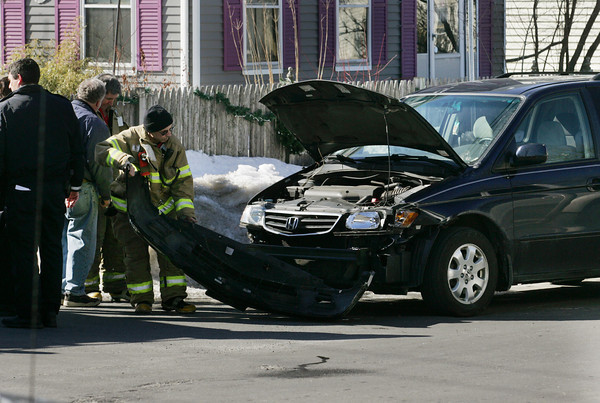 Gloucester: Gloucester firefighter Steve Mitchell removes the bumper from a mini van involved in an accident on the corner of Washinton Street and Centennial Avenue Friday afternoon. Mary Muckenhoupt/Gloucester Daily Times