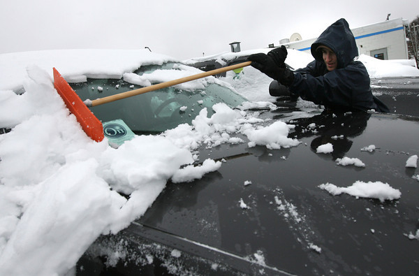 Gloucester: Brad Sudbay brushes snow from one of the 160 cars on the lot at Sudbay Family Automotive Center yesterday. Photo by Kate Glass/Gloucester Daily Times