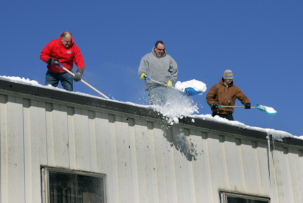 Gloucester: From left, Dave Sauvageau, Bob Charland and Mark Chaisson throw snow off the roof of the Bomco building on Gloucester Avenue alongside after Bomco employees were let out on a half day as a safety precaution Friday afternoon. Mary Muckenhoupt/Gloucester Daily Times