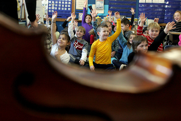 Gloucester: First grade students raise their hands to come up with the next sound effect in the story they were putting together for Sandy Kiefer's Talking Cello program at East Gloucester Elementary School Friday morning. Kiefer came to the school to tell stories with sound effects from her cello like a meowing cat, blowing wind, heavy foot steps and much more. The program was sponsored by the school's PTO. Mary Muckenhoupt/Gloucester Daily Times