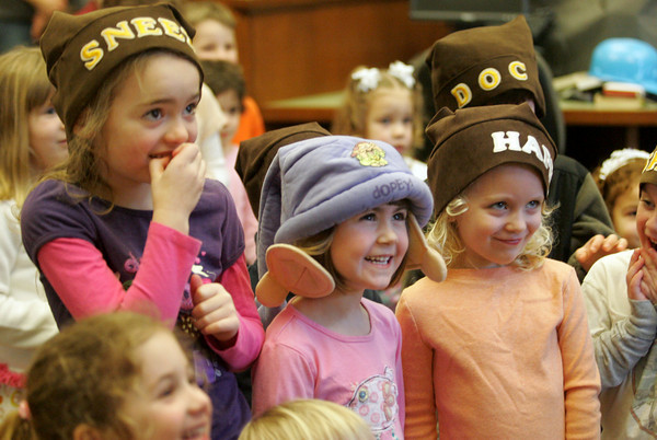 Manchester: From left, Annabel Smith, Emily Parkins and Lucia Logue-Perron, playing Sneezy, Dopey and Happy, watch Snow White, played by Carole Finn, tell her story at the Manchester Public Library Friday morning. Mary Muckenhoupt/Gloucester Daily Times