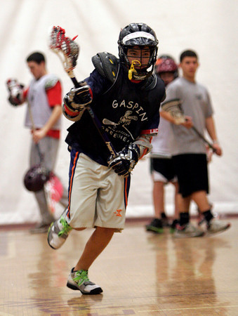 Gloucester: Derek Walker runs with the ball during the Cape Ann Youth Lacrosse Clinic at Gloucester High School on Sunday morning. Current high school players and former college players worked with the kids on different drills preparing them for the season. Photo by Kate Glass/Gloucester Daily Times