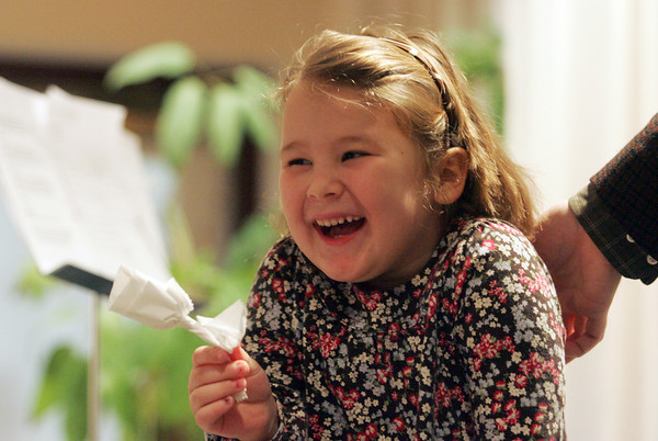 Rockport: Emily Hale, 5, giggles after Danno Sullivan, the ukulele man, gives her a rose he made from a paper napkin at the Rockport Public Library Saturday morning. Mary Muckenhoupt/Gloucester Daily Times
